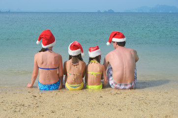 Family in santa hats on beach, new year and christmas holiday