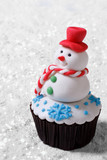 Cupcake Christmas snowman on white snow. vertical