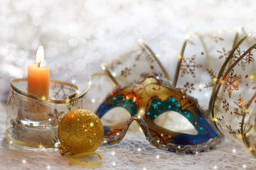 Christmas still life with mask, ribbons, balls and candles