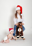 two children in Santa hats with a horse