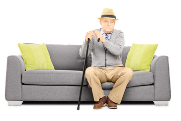 Thoughtful senior man with a cane sitting on a sofa