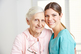 Caregiver embracing happy senior woman