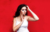 Beauty portrait of woman with colorful makeup on red backround