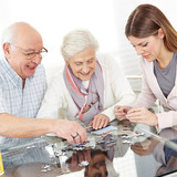 Senior couple solving jigsaw puzzle with family