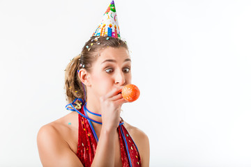 Woman celebrating birthday blowing up balloon