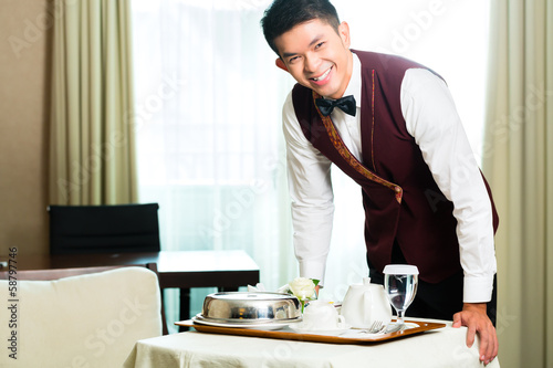 Asian Chinese room service waiter serving food in hotel