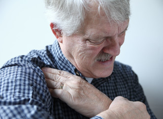 man suffering from shoulder pains