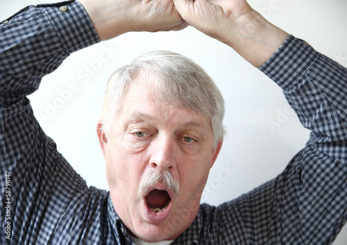 tired older man stretches and yawns
