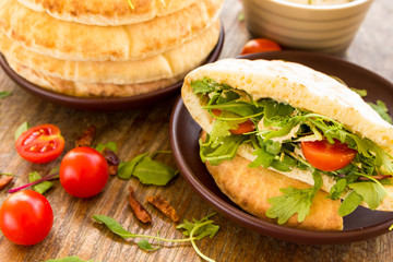Pita with tomatos, cheese and salad mix
