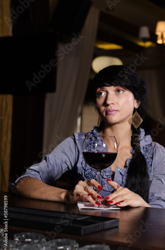 Sad thoughtful woman drinking at the pub