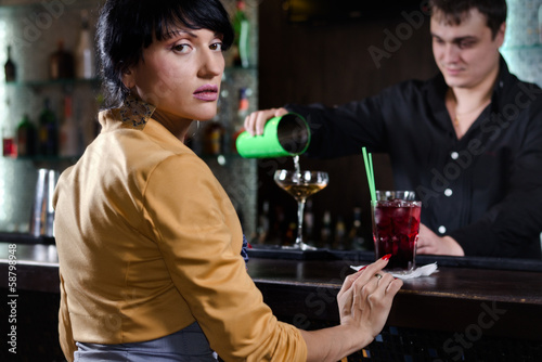 Woman sitting at a bar waiting to be served