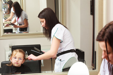 Hairdresser straightening hair little girl child in salon