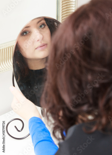 Curly woman looking at mirror by hairstylist