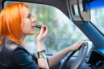 Woman driver painting her lips while driving a car