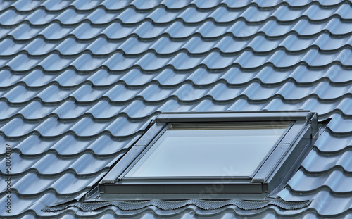Roof window on a grey tiled rooftop, large detailed loft skyligh