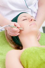 Woman and stimulating facial treatment therapist. Spa.