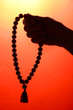 male hand with rosary, on red background