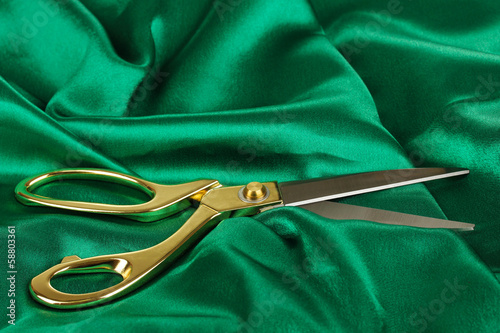 Metal scissors on green fabric