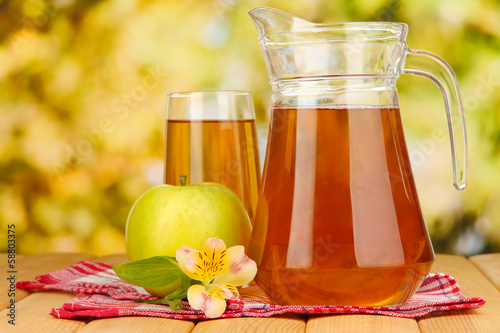 Full glass and jug of apple juice and apple