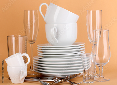 Clean white dishes on beige background