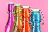Colorful bottles on pink background