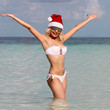 Happy Santa Girl on Tropical Beach. Beautiful blonde young woman