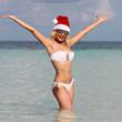 Happy Santa Girl on Tropical Beach. Beautiful blonde young woman