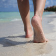 Female Feet on Tropical Sand Beach. Legs Walking.