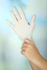 Doctor putting on protective gloves, on light background