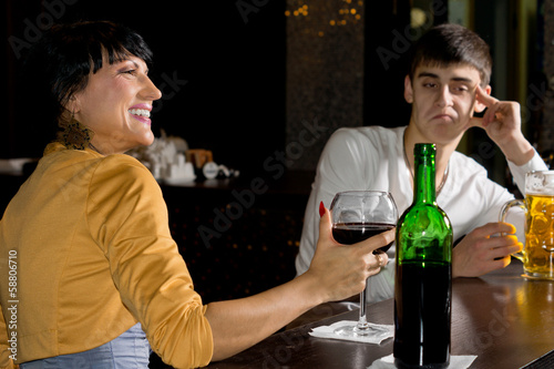 Optimistic woman drinking red wine at the bar