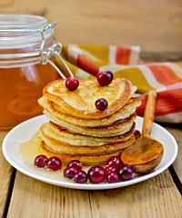 Flapjacks with cranberry and a jar of honey on the board