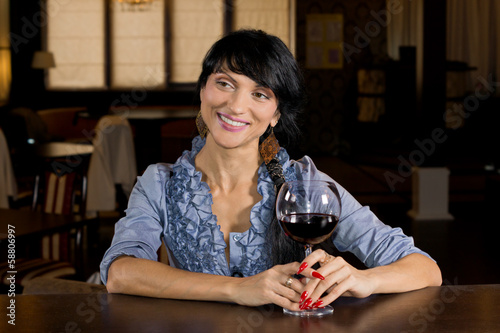 Flirtatious young woman drinking at a bar