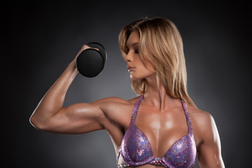 Sexy blond bodybuilder girl with dumbbells.