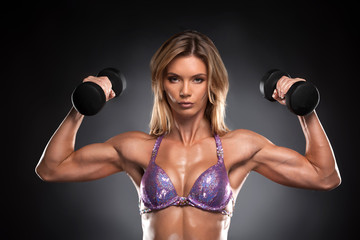 Sexy fit muscular woman posing with dumbbells.