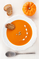 Pumpkin soup with croutons and pumpkin seeds in a white plate