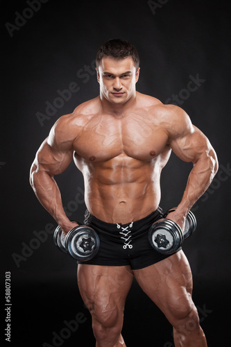 Sexy muscular bodybuilder lifting dumbbell.