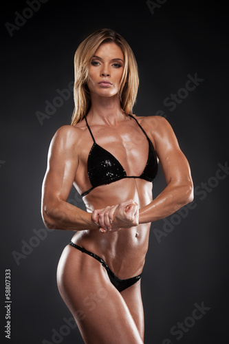 Sexy blond bodybuilder woman in black bikini.