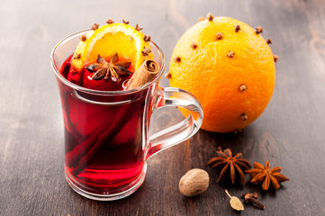 Hot mulled wine in glass with orange and spices