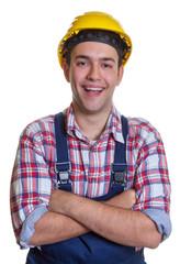 Lachender Bauarbeiter mit verschränkten Armen