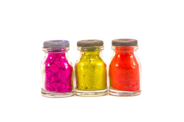 three colorful indian ritual paint bottles isolated on white