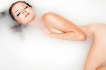 Beauty and spa woman in milk and honey bath
