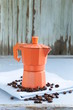 orange metal сoffee maker and  beans on blue background