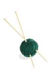 Ball of green thread and knitting spokes