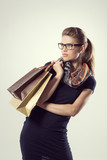 Glamour lady in stylish dress and eyeglasses holding bags