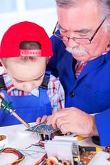 Grandfather teaching grandchild soldering with iron