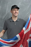 Smiling man in gray against background of the British flag