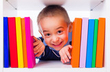 Little boy looking through book shelf