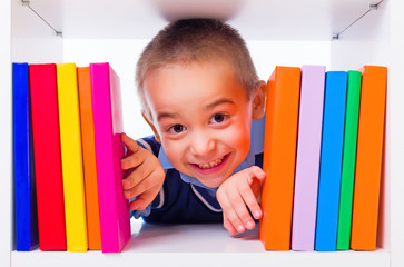 Little boy looking through book shelf