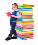 Little boy reading near big stack of books