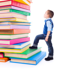 Little boy looking up to stacked big books